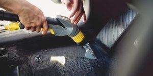 Professional detailer vacuuming carpet of car interior, using steam vacuum