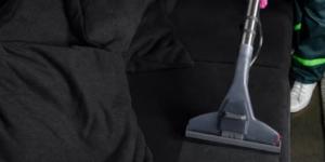 Upholstery cleaner on black sofa